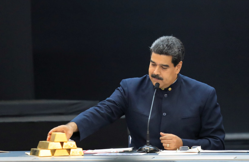 Venezuela's President Maduro touches a gold bar as he speaks during a meeting with the ministers responsible for the economic sector in Caracas (photo credit: MARCO BELLO/REUTERS)