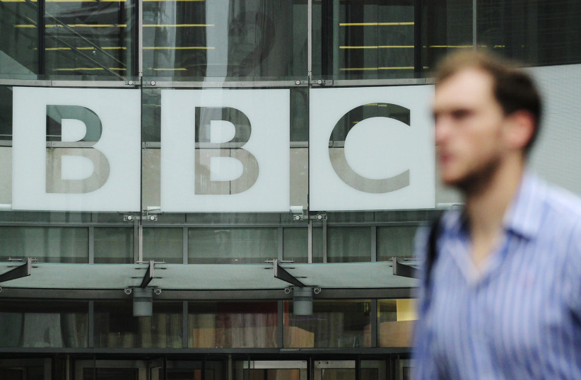 A pedestrian walks past a BBC logo at Broadcasting House in central London (photo credit: OLIVIA HARRIS/ REUTERS)