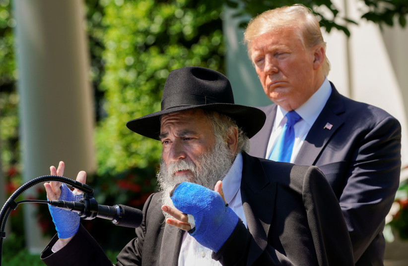 Rabbi Yisroel Goldstein, injured in the recent shooting at the Congregation Chabad synagogue in Poway, California, speaks as U.S. President Donald Trump looks on, May 2, 2019 (photo credit: KEVIN LAMARQUE/REUTERS)
