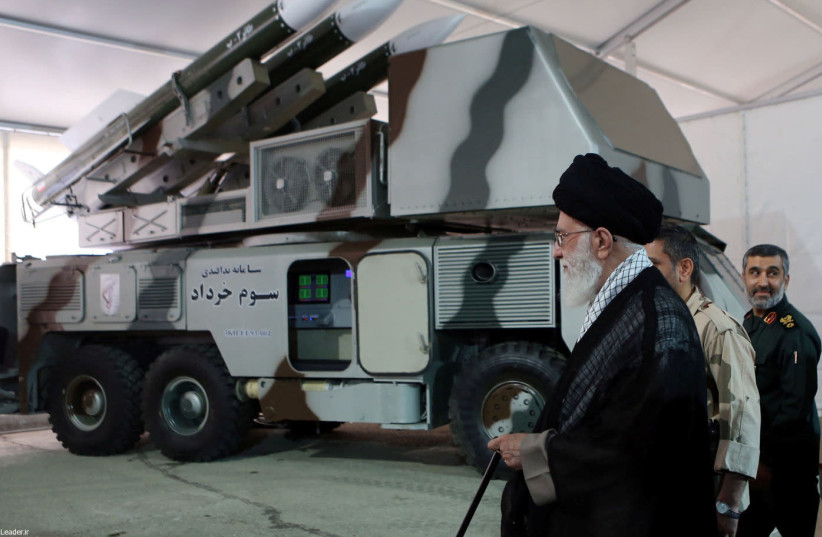 """Iran's Supreme Leader Ayatollah Ali Khamenei is seen near a """"3 Khordad"""" system which is said to had been used to shoot down a U.S. military drone, according to news agency Fars, in this undated handout picture (photo credit: FARS NEWS/HANDOUT VIA REUTERS)"""