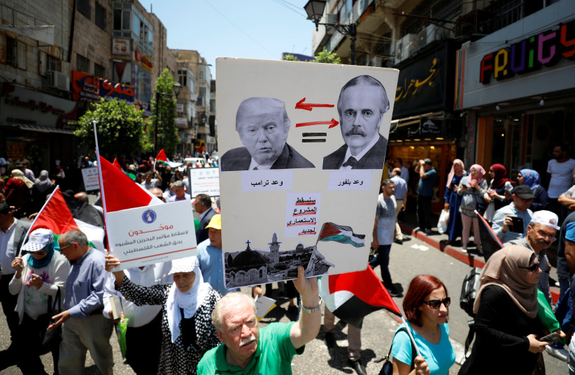 Palestinians take part in a protest against Bahrain's workshop for U.S. peace plan, in Ramallah, in the West Bank (photo credit: MOHAMAD TOROKMAN/REUTERS)