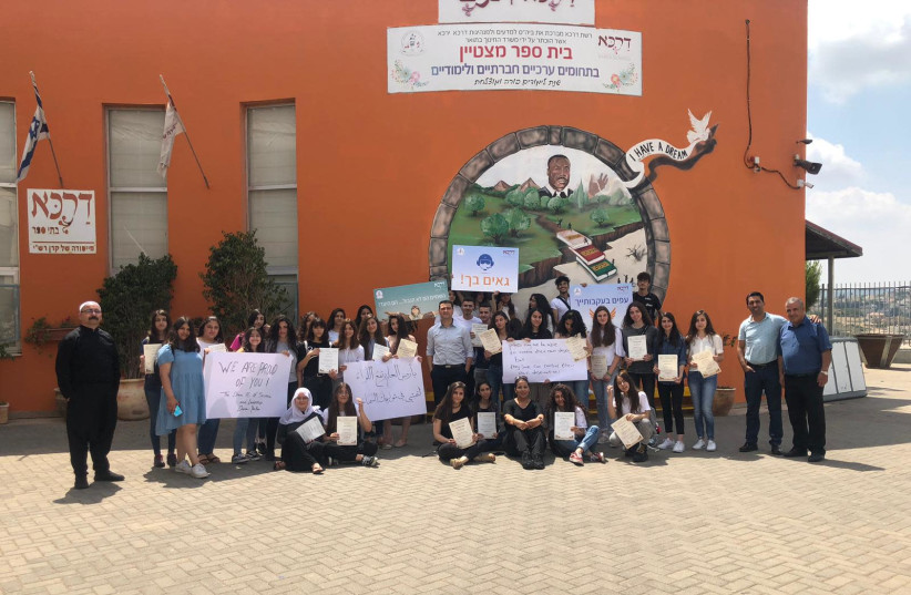 Students and staff of the school where G. graduated from in a picture congratulating him (photo credit: DARCA)