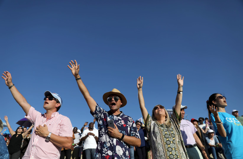 Christian pilgrims and tourists react during a religious retreat lead by T.B. Joshua, a Nigerian evangelical preacher on Mount Precipice, Nazareth (photo credit: AMMAR AWAD / REUTERS)