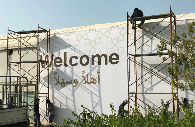 """Workers place a banner at the pavilion where the U.S. hosted event """"Peace to Prosperity"""" takes place outside Four Seasons Hotel in Manama, Bahrain. (photo credit: MATT SPETALNICK/REUTERS)"""