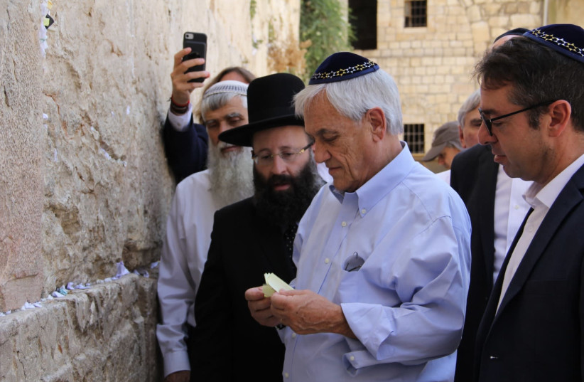 Chile's President Sebastian Pinera places notes from the Anne Frank school in Santiago into the Western Wall (photo credit: WESTERN WALL HERITAGE FOUNDATION)