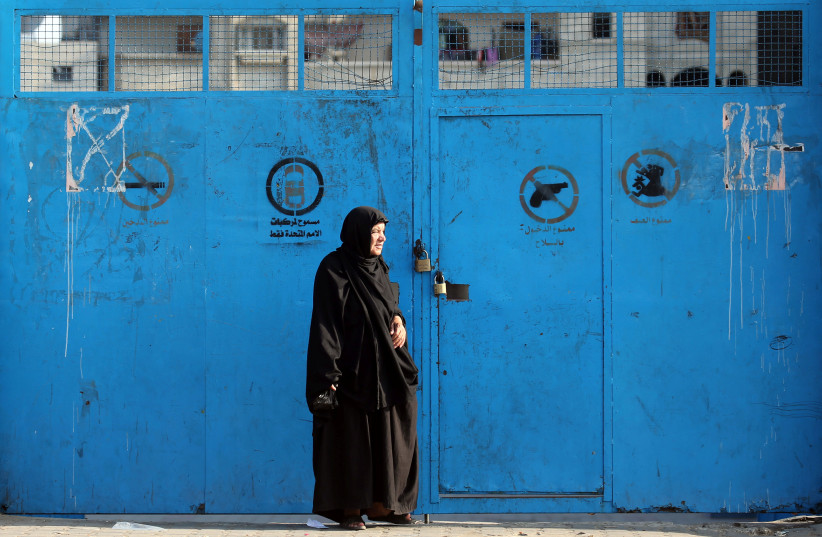 A Palestinian woman stands outside a closed school run by the United Nations Relief and Works Agency (UNRWA), during a strike by the agency's employees union to protest against job cuts, in Khan Younis in the southern Gaza Strip October 2, 2018 (photo credit: IBRAHEEM ABU MUSTAFA / REUTERS)