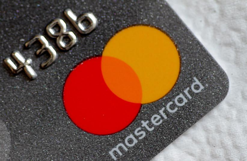 Illustration photo of a Mastercard logo on a credit card (photo credit: THOMAS WHITE / REUTERS)