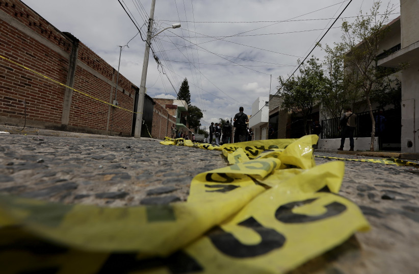 Yellow police tape lies on the road as federal agents work at a crime scene in the town in Mexico  (photo credit: ALEJANDRO ACOSTA/REUTERS)
