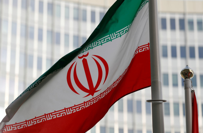 The Iranian flag flutters in front of the International Atomic Energy Agency (IAEA) headquarters in Vienna last March (photo credit: REUTERS/LEONHARD FOEGER)