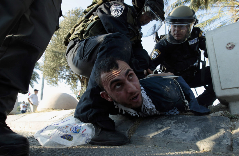 Israeli policemen detain a protester during clashes in the Israeli-Arab town of Umm el-Fahm (photo credit: AMMAR AWAD/REUTERS)