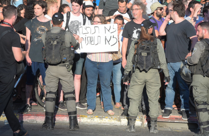 A protester holding a sign saying 'Thou shalt not kill, thou shalt not be silent'   (photo credit: AVSHALOM SASSONI)