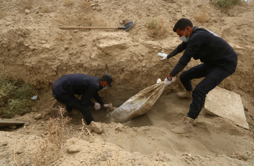 Workers pull an unidentified body at a mass grave in Raqqa, Syria October 16, 2018. Picture taken October 16, 2018. (photo credit: ABOUD HAMAM / REUTERS)
