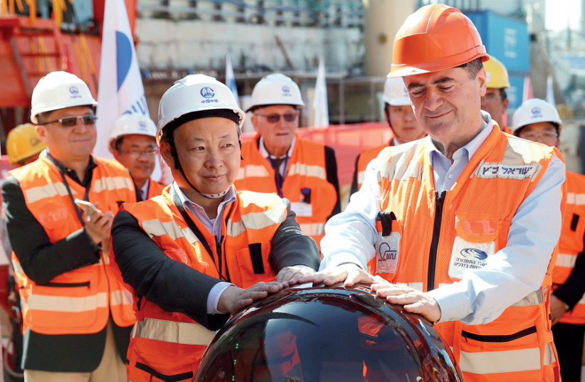 Previous transportation minister Israel Katz and employees of the China Railway Engineering Corporation take part in an event in 2017 marking the beginning of underground construction work of the Tel Aviv light rail, using a Tunnel Boring Machine (TBM) (photo credit: BAZ RATNER/REUTERS)