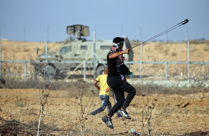 A Palestinian demonstrator uses a sling to hurl stones at Israeli forces during a protest at the Israel-Gaza border fence, in the southern Gaza Strip June 21, 2019 (photo credit: IBRAHEEM ABU MUSTAFA / REUTERS)