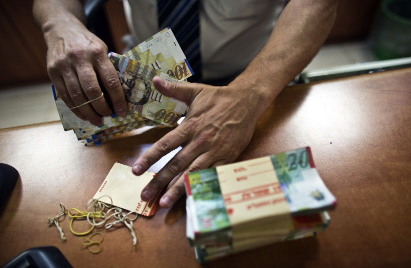 A bank employee counts Israeli Shekel notes for the camera at a bank branch in Tel Aviv (photo credit: REUTERS)
