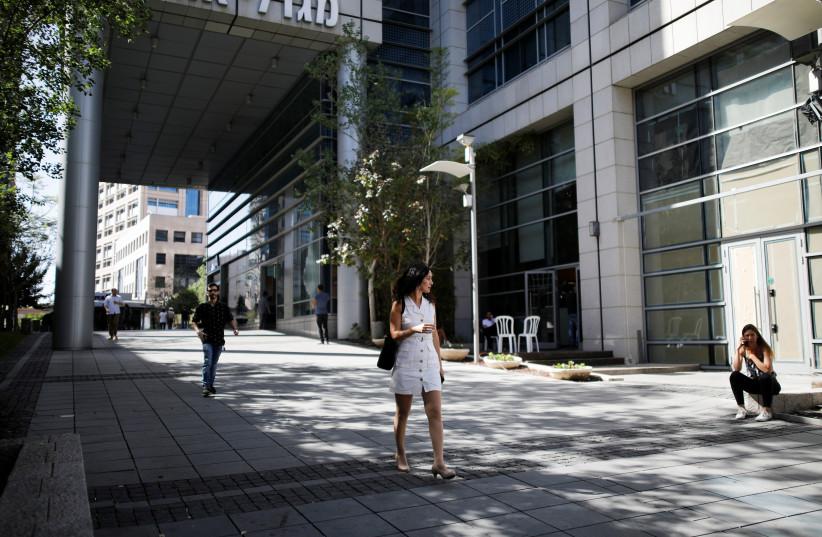A woman walks near high-rise buildings in the high-tech business area of Tel Aviv (photo credit: REUTERS/AMIR COHEN)