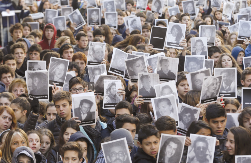 MEMBERS OF THE Argentinean Jewish community in Buenos Aires hold up pictures of the victims of the AMIA Jewish center bombing, during a ceremony in 2015 to mark the 21th anniversary of the 1994 attack (photo credit: ENRIQUE MARCARIAN / REUTERS)