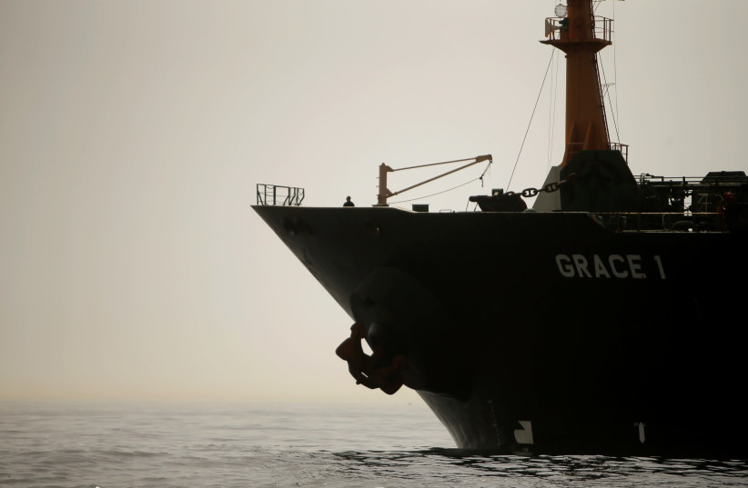 A crew member of the Iranian oil tanker Grace 1 is seen on the bow as it sits anchored after it was seized earlier this month by British Royal Marines off the coast of the British Mediterranean territory (photo credit: JON NAZCA/ REUTERS)