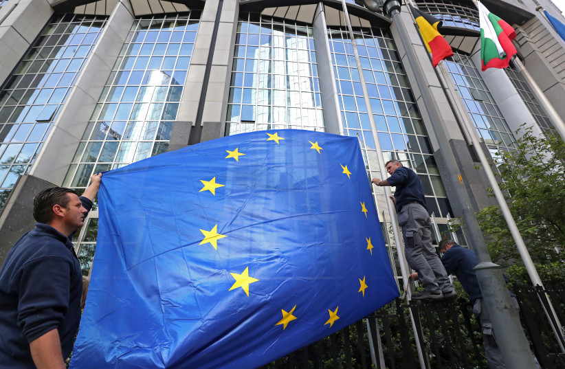 Workers adjust a European flag outside the EU Parliament ahead of the EU elections in Brussels (photo credit: YVES HERMAN / REUTERS)