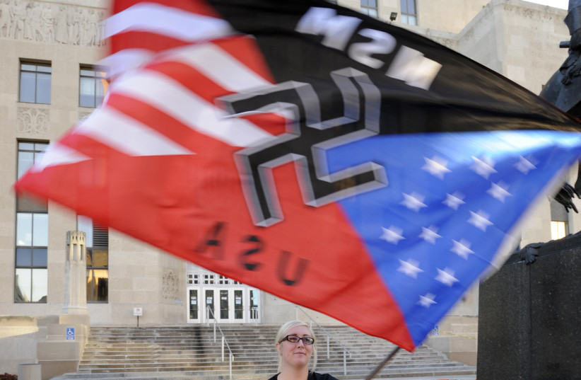 A supporter waves her flag during a neo-Nazi rally at the Jackson County Courthouse in Kansas City, Missouri (photo credit: DAVE KAUP / REUTERS)