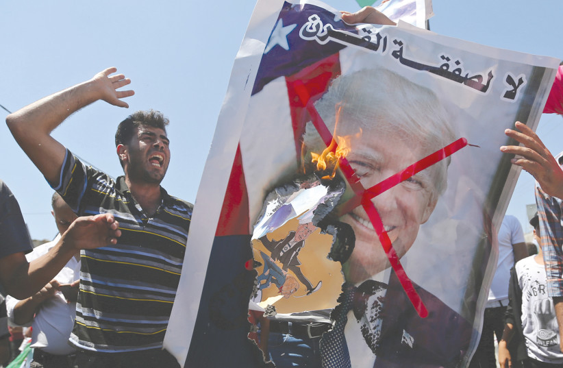 PALESTINIAN DEMONSTRATORS burn a crossed-out poster depicting US President Donald Trump that reads: 'no for Deal of the Century' during a protest against the Bahrain workshop last month. (photo credit: IBRAHEEM ABU MUSTAFA / REUTERS)
