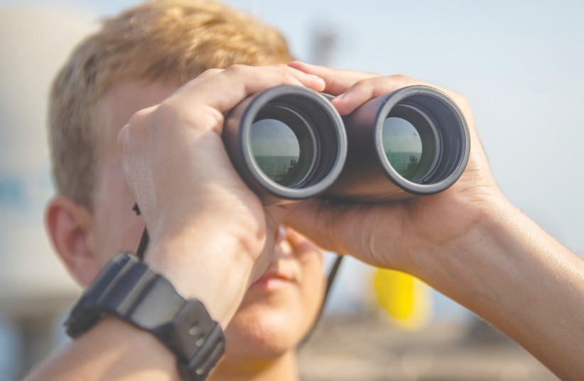 A US SEAMAN scans the horizon during his watch aboard the US Navy Arleigh Burke-class guided-missile destroyer USS Bainbridge in the Arabian Gulf this week.  (photo credit: JASON WAITE/REUTERS)