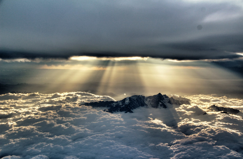 """Sun penetrating the clouds above the mountains near Chengdu, China. """"It looks like Genesis to me,"""" says Tomer (photo credit: TOMER ZADOK)"""