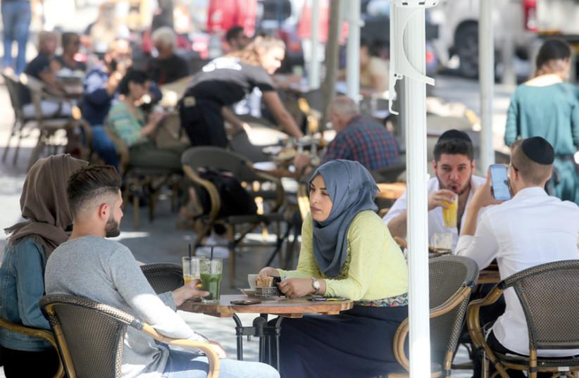 Arab Israelis and Haredi youth at a café in Jerusalem (photo credit: MARC ISRAEL SELLEM)
