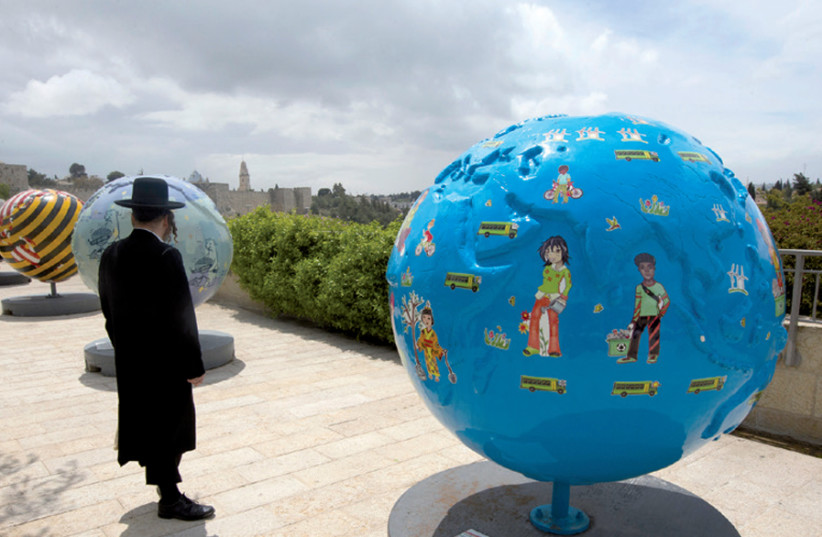 An ultra-Orthodox man observes the giant globes displayed outside the walls of Jerusalem's Old City; the initiative of the non-profit organization Cool Globes aims to raise awareness of climate change (photo credit: RONEN ZVULUN)