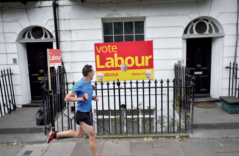 A man runs past a Labour Party sign with pictures of both Jeremy Corbyn and Britain's new prime minister, Boris Johnson, in north London (photo credit: HANNAH MCKAY/ REUTERS)