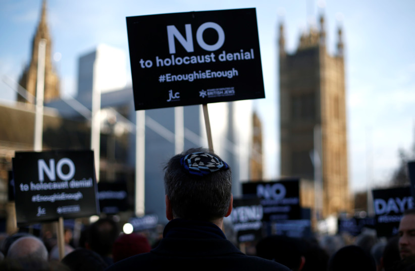 Protesters hold placards and flags during a demonstration, organised by the British Board of Jewish Deputies for those who oppose antisemitism, in Parliament Square in London (photo credit: HENRY NICHOLLS/REUTERS)