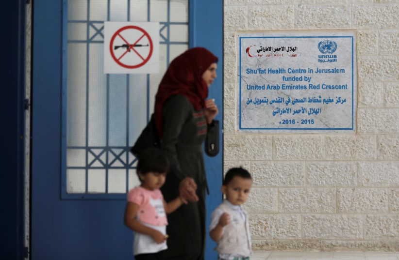 A Palestinian woman walks with her children near an entrance of the UNRWA (United Nations Relief and Works Agency) health center in the Shuafat refugee camp in east Jerusalem October 10, 2018 (photo credit: AMMAR AWAD / REUTERS)