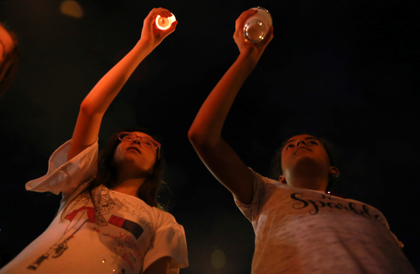 Mourners take part in a vigil near the border fence between Mexico and the U.S after a mass shooting at a Walmart store in El Paso U.S. in Ciudad Juarez (photo credit: REUTERS/CARLOS SANCHEZ)
