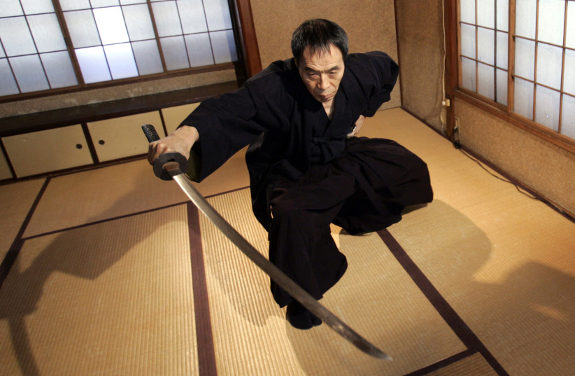 Japanese ancient martial arts master Yoshinori Kouno demonstrates his skills in Tokyo February 14, 2008. The 59-year-old master of Japanese ancient martial arts may never get a chance to test his skills in real combat in the modern world, but some of the country's top athletes are learning from his  (photo credit: YURIKO NAKAO/ REUTERS)