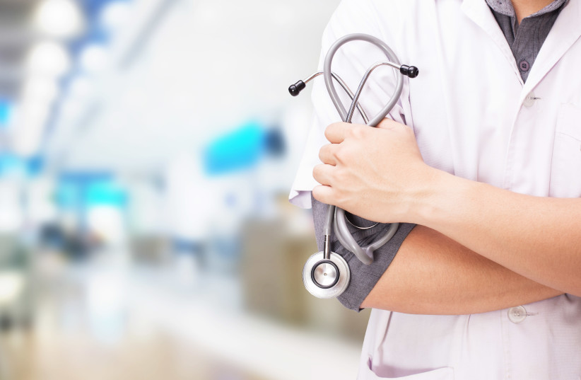 Doctor with a stethoscope in the hands and hospital background (illustrative) (photo credit: INGIMAGE)