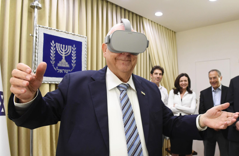 President Rivlin tries on virtual reality goggles at meeting with Sheryl Sandberg, 12 August 2019 (photo credit: Mark Neiman/GPO)
