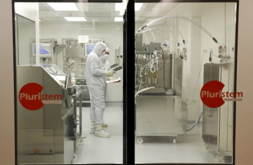Biologists work in a laboratory at Pluristem Theraputics in Haifa (photo credit: REUTERS)