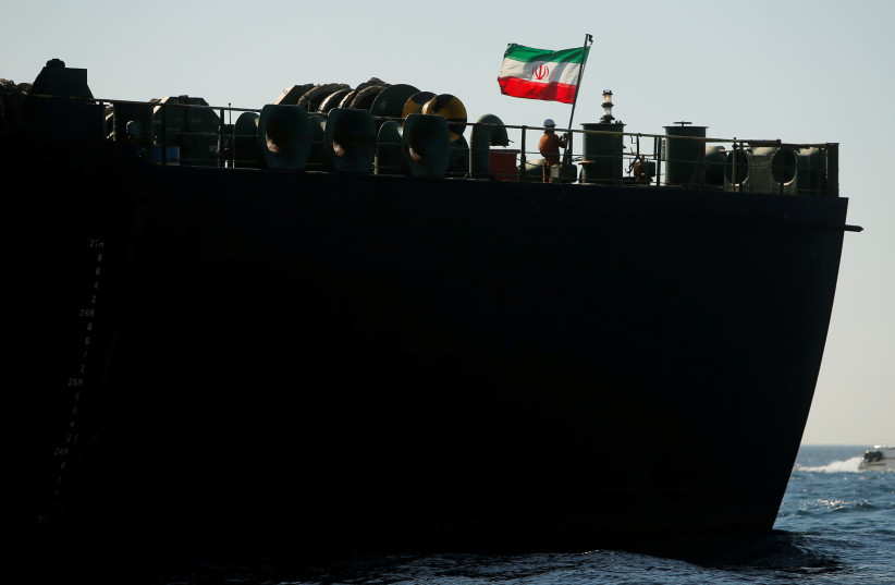 A crew member raises the Iranian flag on Iranian oil tanker Adrian Darya 1, previously named Grace 1, as it sits anchored after the Supreme Court of the British territory lifted its detention order, in the Strait of Gibraltar (photo credit: JON NAZCA/ REUTERS)