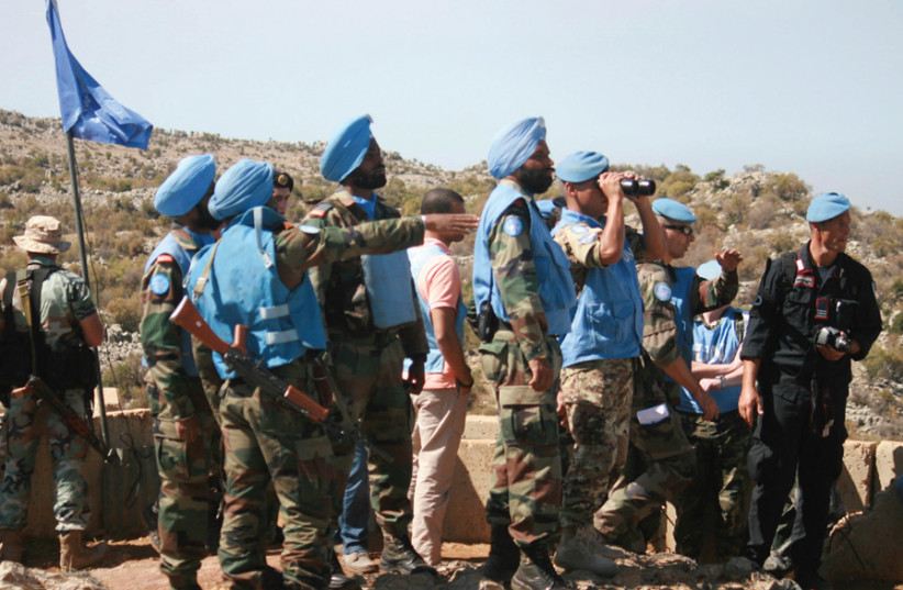 LEBANESE SOLDIERS and UN peacekeepers (blue berets and turbans) serving with UNIFIL inspect areas targeted by IDF shelling in the Shebaa area, southern Lebanon, on October 8, 2014. (photo credit: REUTERS/KARAMALLAH DAHER)