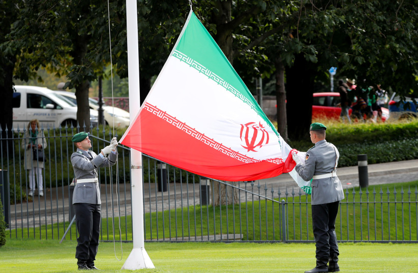 Soldiers of the German armed forces Bundeswehr hold the Iranian flag during a ceremony for the diplomatic accreditation of the new ambassador of Iran to Germany in Berlin (photo credit: FABRIZIO BENSCH / REUTERS)
