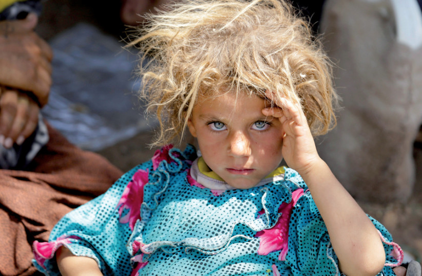A girl from the Yazidi sect fleeing the violence in Sinjar rests at the Iraqi-Syrian border crossing in Fishkhabour, Dohuk province, in 2014 (photo credit: YOUSSEF BOUDLAL / REUTERS)