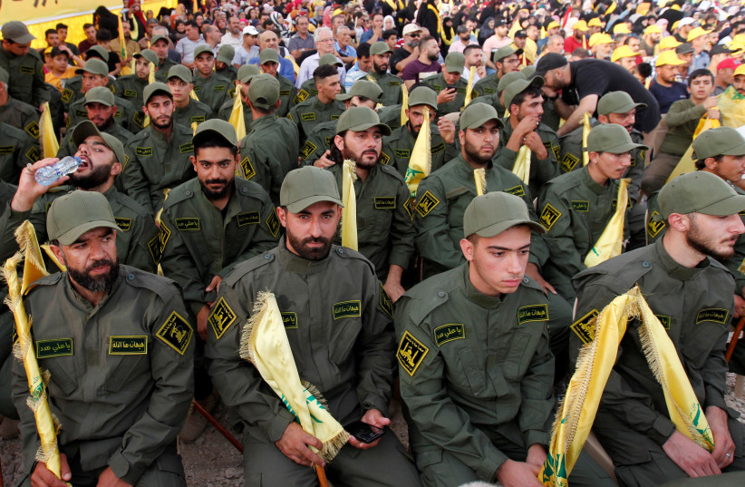 Lebanon's Hezbollah members hold party flags as they listen to their leader Sayyed Hassan Nasrallah addressing his supporters via a screen during a rally marking the anniversary of the defeat of militants near the Lebanese-Syrian border, in al-Ain village, Lebanon August 25, 2019.  (photo credit: REUTERS)