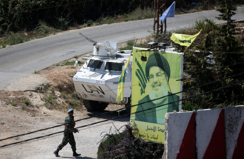 A U.N peacekeeper of the United Nations Interim Force in Lebanon (UNIFIL) walks near a poster depicting Lebanon's Hezbollah leader Sayyed Hassan Nasrallah (photo credit: REUTERS)