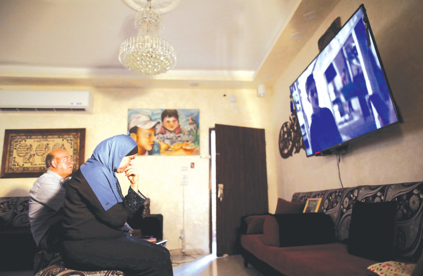 Hussein and Suha Abu Khdeir, whose son's murder is the subject of the HBO series 'Our Boys', watch the show's first two episodes in their East Jerusalem home in mid August. (photo credit: REUTERS/AMMAR AWAD)