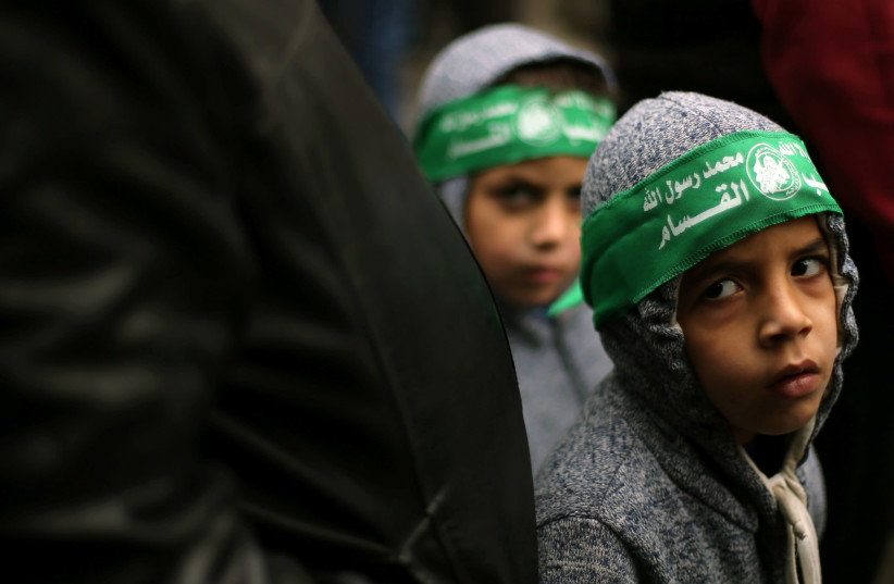 Palestinian children wearing Hamas headbands take part in a rally against U.S. President Donald Trump's decision to recognize Jerusalem as the capital of Israel, in the Gaza Strip (photo credit: IBRAHEEM ABU MUSTAFA/REUTERS)
