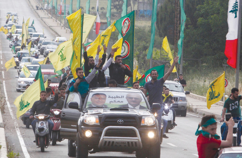 Supporters of Lebanon's Hezbollah and Amal movement gesture as they ride in a car in Marjayoun  (photo credit: REUTERS)