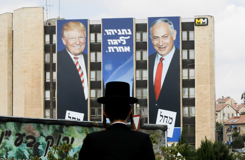 A haredi man stares at a Likud ad with Prime Minister Benjamin Netanyahu and US President Donald Trump. (photo credit: MARC ISRAEL SELLEM)