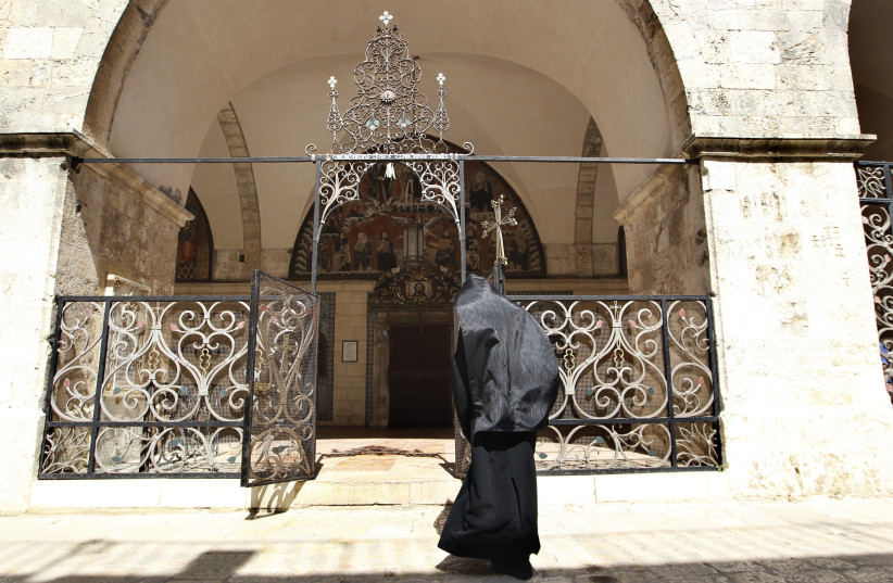 An Armenian priest enters a church at the monastery compound in the Armenian Quarter in Jerusalem's Old City June 8, 2010. The Armenians in Jerusalem now fear their 1,500-year-old Christian presence may disappear. Their society and extensive landholdings risk becoming collateral damage in a demograp (photo credit: REUTERS)
