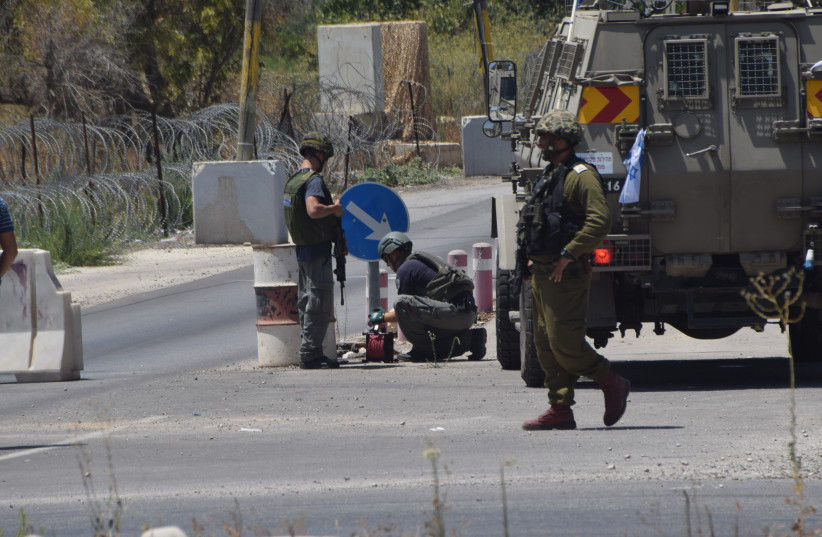 IDF soldiers and bomb technicians after disarming the bomb at the 'Focus' Checkpoint near the entrance to the community of Beit El in Binyamin. Aug 03, 2016 (photo credit: INBAL REUVENI/ TPS)
