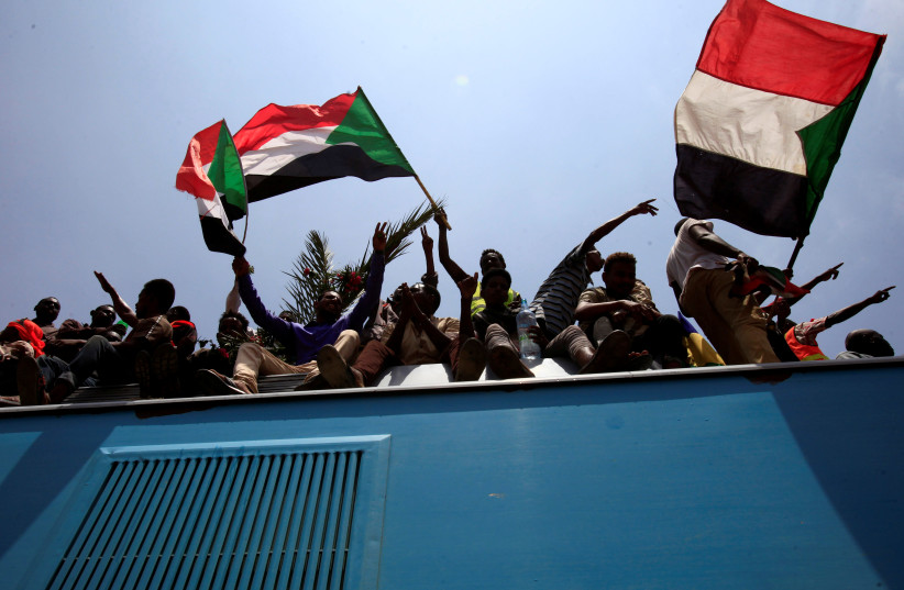 Sudanese civilians wave their national flags during the signing of the Sudan's power sharing deal, Khartoum (photo credit: REUTERS/MOHAMED NURELDIN ABDALLAH)